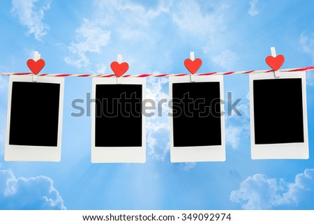 4 Blank instant photo and red clip paper heart hanging on the clothesline with blue sky nature and cloud background..Designer concept. - stock photo