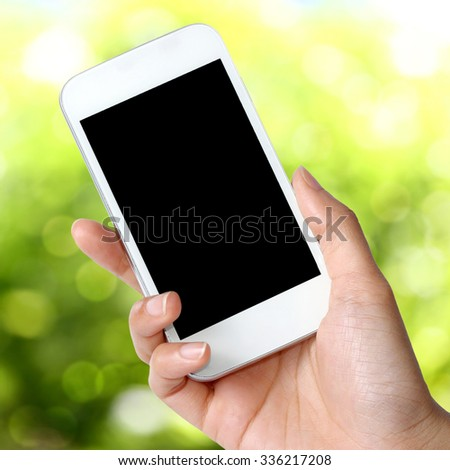 Blank screen mobile phone in hand  on green field background - stock photo