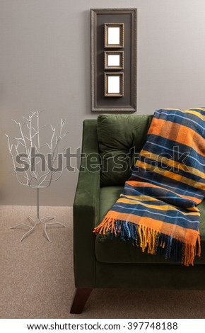 blanket green armchair with old frame grey wall decor - stock photo