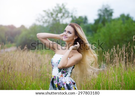 blond girl in dress  on a meadow - stock photo