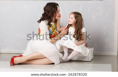 blond little girl playing with  her mother - stock photo