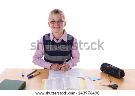 blond teenage boy with glasses wearing a hooped sweater. He sits at his desk and making fun and enthusiasm with his homework, isolated against white background. - stock photo