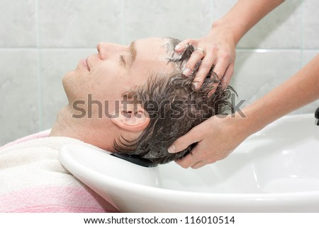 blonde in a salon getting washed her hair with shampoo - stock photo