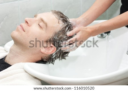 blonde in a salon getting washed her hair with shampoo