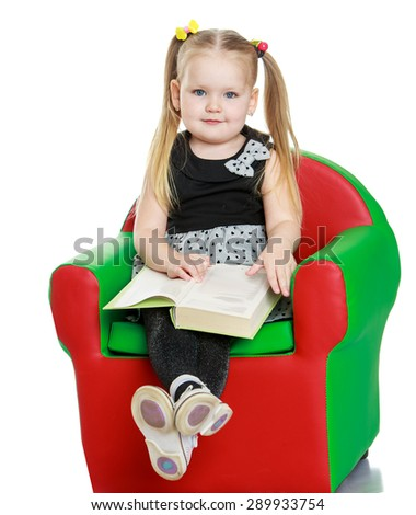 Blonde little girl reading a book sitting on the chair- isolated on white background - stock photo