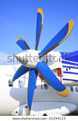 Blue and yellow wing with propeller of the passenger plane - stock photo