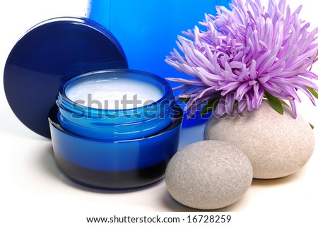 blue cosmetic cream,lotion, candle, flower on white