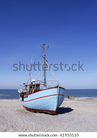 blue fishing cutter on shore - stock photo