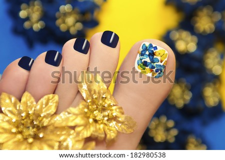 Blue pedicure with butterflies in white lacquer big toe with Golden flowers. - stock photo