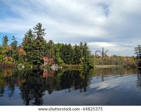 Blue skies and fair-weather clouds reflected along with autumn foliage, in the serene water of a New England lake. - stock photo