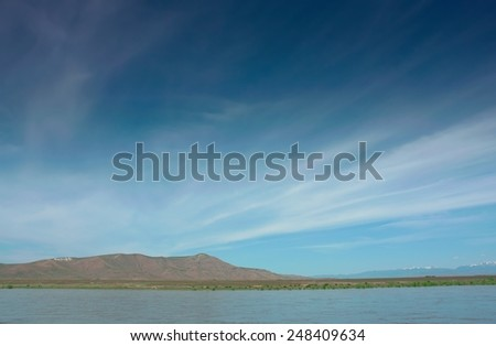 Blue sky with filamentary clouds,  mountains and river - stock photo