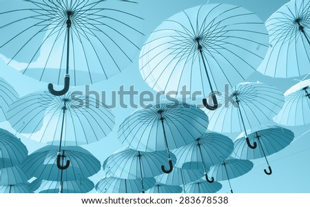 blue umbrellas under the beautiful cloudy sky. colorful summer  - stock photo
