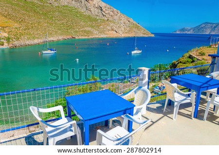 Blue wooden tables and chairs with view on sea bay on Greek Island, southern Greece - stock photo