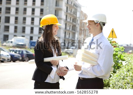 Blueprints and Handshake on construction site. - stock photo