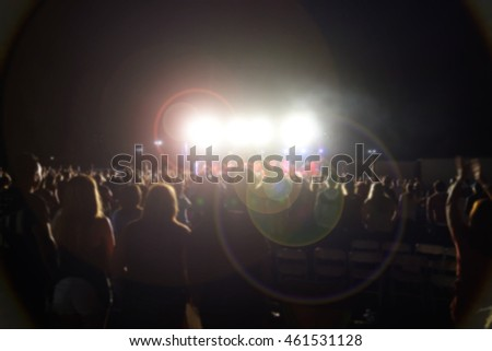 blur background of people at concert with bright lights and lens flare