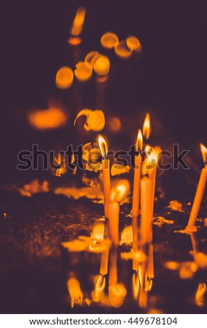 blurred candle flame light at night with bokeh on dark background - stock photo