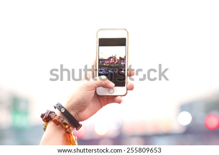 blurred people take photo , hand hold phone take photo in concert and travel up to sky with purple light background, internet and communication lifestyle.