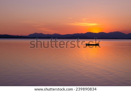 """boat"" a boat moored in the middle of a pond framed by a sunset conveys a sense of peace and relaxation - stock photo"