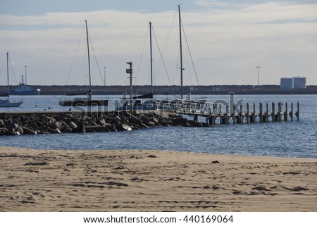 Boat launch jetty on Koombaba Beach, Bunbury, South Western Australia  on a cloudy morning in early winter is calm with gentle waves.