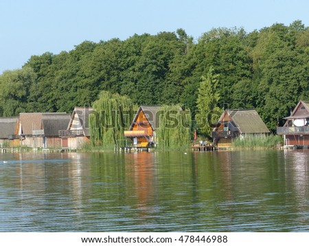 Boathouses in the morning mist on the banks of Mueritz Arms. Germany