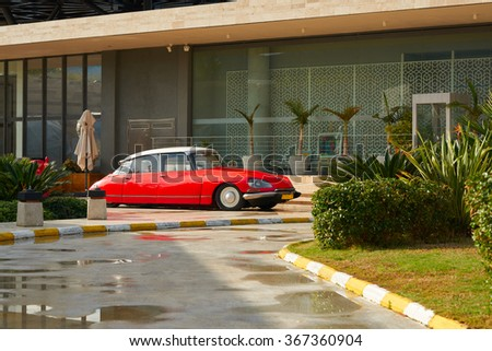 BODRUM / TURKEY �  22 JANUARY 2016:  Red luxury vintage car Citroen DS parked at the front of the restaurant near beautiful garden in Palmarina, Bodrum, Turkey - stock photo