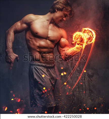 bodybuilder showing his great body and holding  dumbell.on fire - stock photo