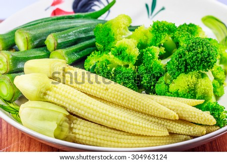 Boiled green roselle,  baby corn and Broccoli on wood table - stock photo