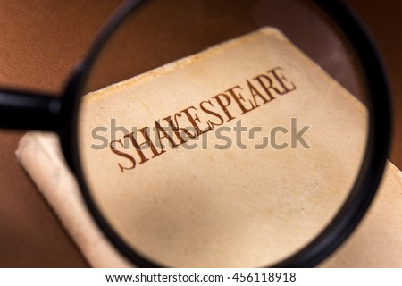 Book by Shakespeare on Vintage Background Viewed through Magnifying Glass