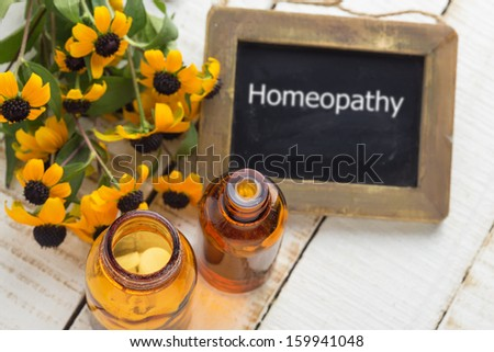 Bottles with medicines on white table. Concept of homeopathy. Selective focus. - stock photo