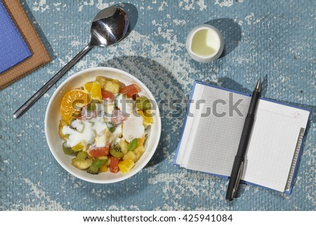 bowl with fruit salad , notebook. Proper nutrition, diet - stock photo