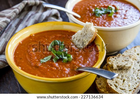 2 bowls of homemade tomato basil soup with spoons sitting on wooden table with brown striped napkin and slices of whole grain bread