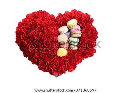 box in the form of heart, is filled by flowers and cookies.  Red carnations, white background.
