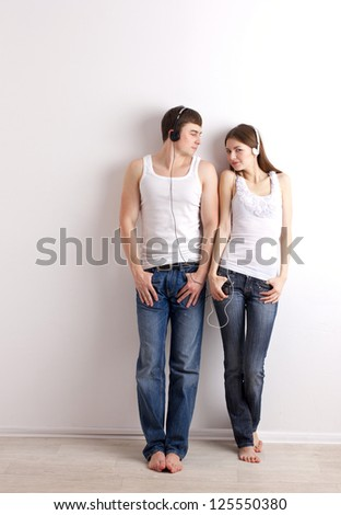 boy and young girl in headphones  listening of a music on  wall background - stock photo