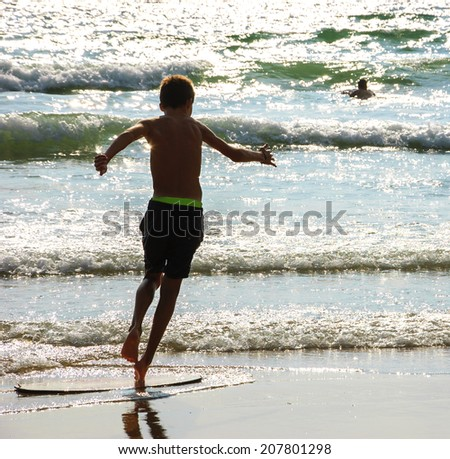 Boy moves on the surf board (alongside the sea shore) and a man swimming in the waves. Back view. (Brittany, France) - stock photo