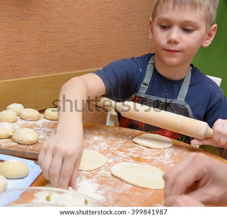 boy  rolling dough with a large wooden rolling pin as he prepares the cakes