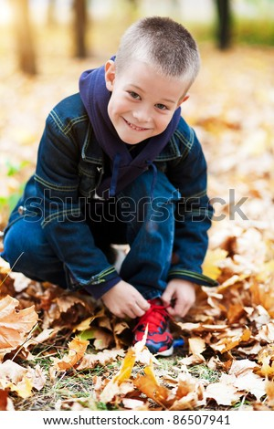 boy sitting in the yellow leaves - stock photo