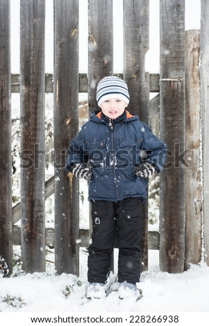 boy stands in a wooden old fence swept up by snow - stock photo