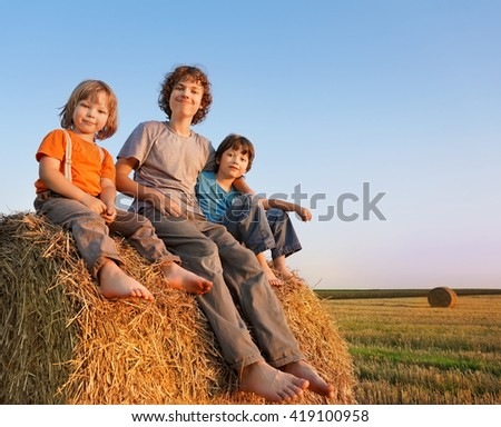 3 boys in a haystack in the field in autumn