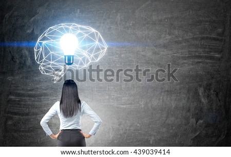 Brainstorming concept with thoughtful businesswoman looking at chalkboard with illuminated polygonal brain sketch and abstract light bulb - stock photo