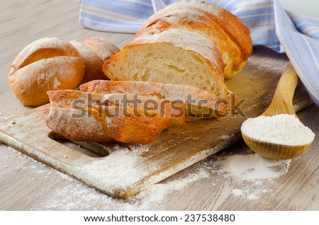 Bread and bread slices on  wooden background. Selective focus - stock photo