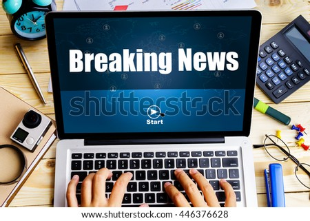 """Breaking News"" word on screen laptop with man hand work on it on wooden table with camera, spectacles, clock, pen and calculator - business, website, travel and blogging concept - stock photo"