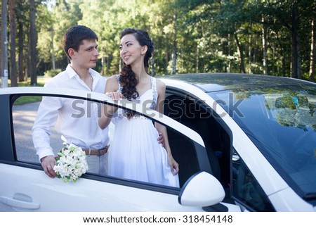 bride and groom near the car, young happy couple - stock photo