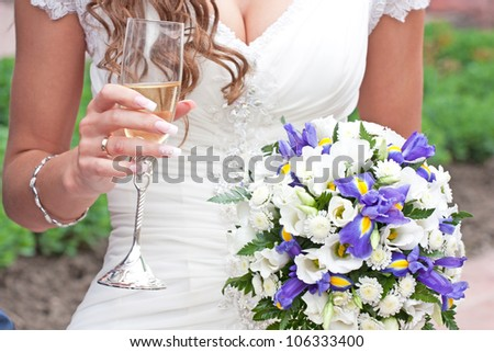 bride holds in hand glass of champagne and wedding bouquet