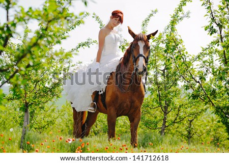 Bride with sorrel horse in blossoming garden