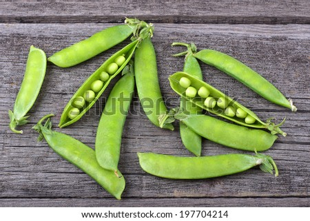 Broad beans of peas on old wood background - stock photo