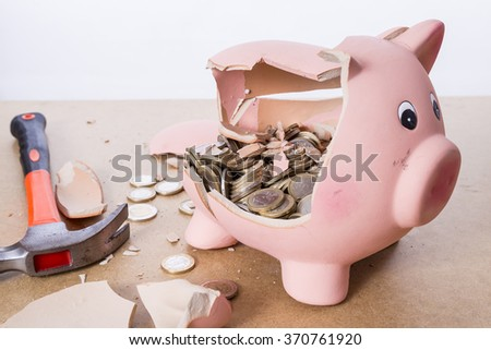 broken piggy bank with hammer and money - stock photo