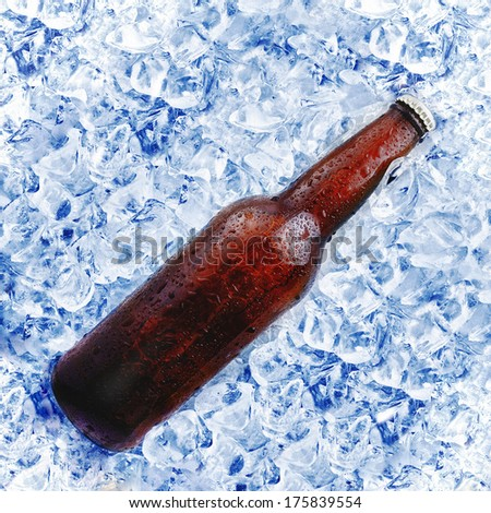 brown beer bottle in ice bucket with condensation - stock photo