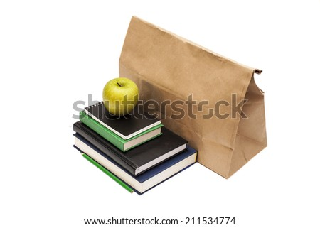 Brown paper bag and green apple on top of textbooks on white background - stock photo