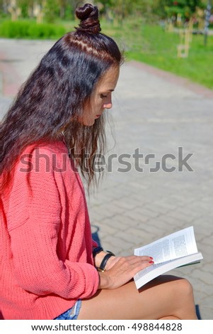 Brunette woman in a red sweater, sitting on a bench and reading a book