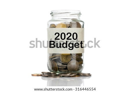 """2020 Budget"" text label on full coins of jar spill out from it isolated on white background - saving, donation, financial, future investment and insurance concept - stock photo"